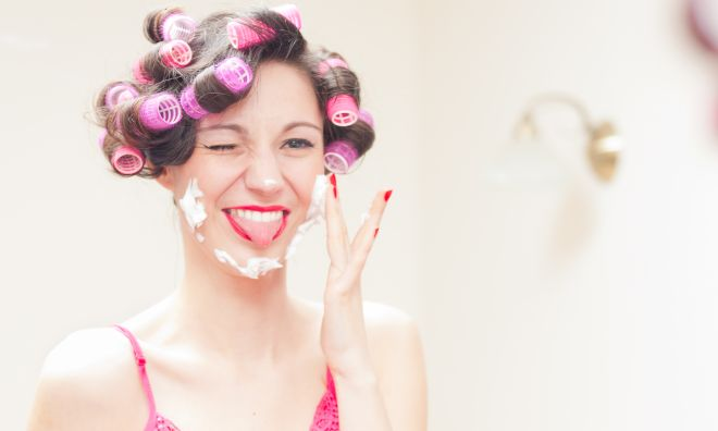 Beautiful funny girl applying shaving foam to her face
